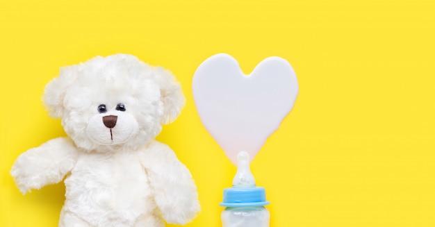 Бутылка молока для ребенка с игрушкой белого медведя на синем фоне. Premium Фотографии
