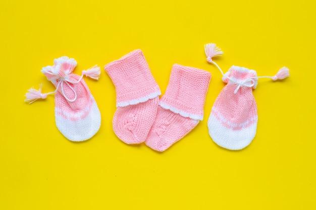 赤ちゃんの手袋と黄色の背景に靴下。 Premium写真