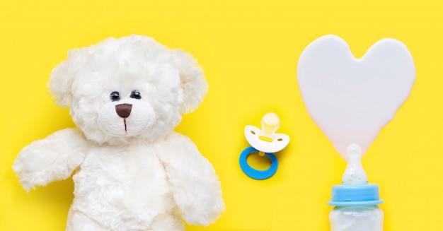 Бутылка молока для младенца и соски с игрушечным мишкой на желтом Premium Фотографии