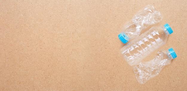 Пластиковая бутылка на фоне фанеры. Premium Фотографии