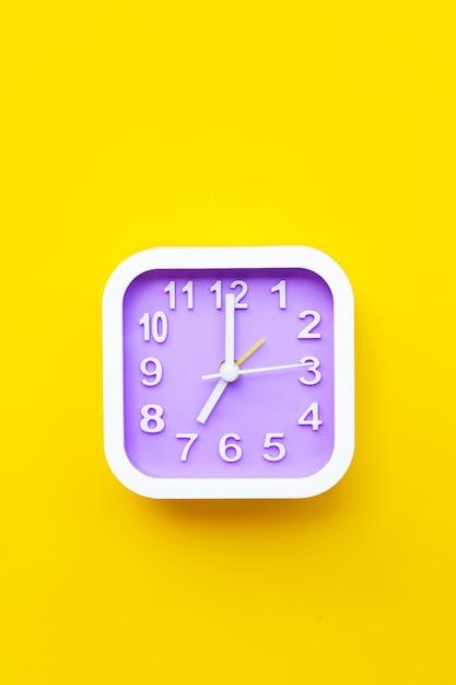 Часы на желтом фоне. Premium Фотографии