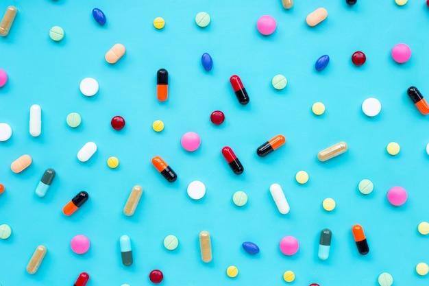 カプセルと青色の背景に丸薬のカラフルな錠剤。 Premium写真