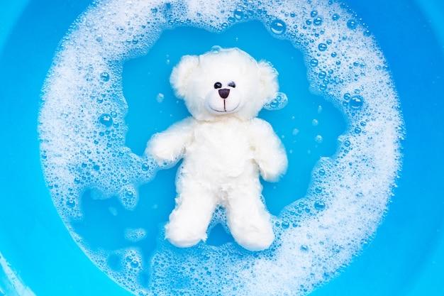 おもちゃのクマを洗濯前に洗濯洗剤の水に浸してください。ランドリー 、 Premium写真