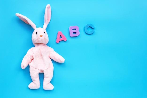 青色の背景に英語のアルファベットとウサギのおもちゃ。教育コンセプト Premium写真