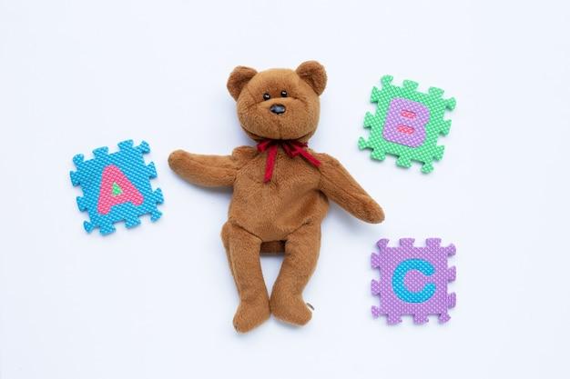 Игрушка бурого медведя с головоломкой английского алфавита концепция образования. Premium Фотографии