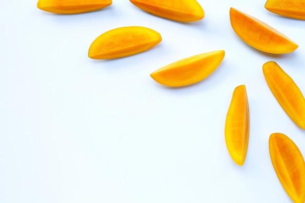 Тропический фрукт, кусочки манго на белой поверхности. Premium Фотографии
