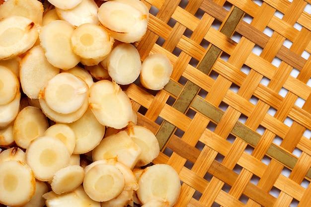 Свежие ломтики галангала на деревянной бамбуковой обмолоте Premium Фотографии