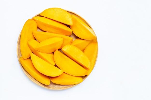 Тропический плодоовощ, куски манго на деревянной плите на белой предпосылке. Premium Фотографии