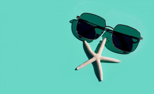 Солнечные очки с рыбами звезды на голубой предпосылке. наслаждайтесь концепцией отдыха. Premium Фотографии