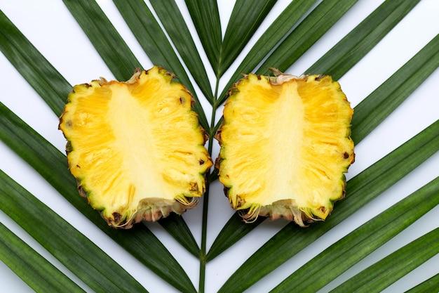 Спелый ананас на тропических пальмовых листьев. вид сверху Premium Фотографии