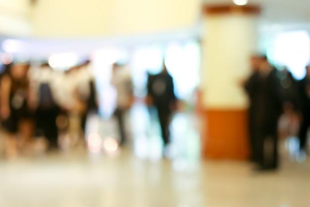立ち上がってロビーを歩いているビジネス人々の活動がぼやけています。 Premium写真