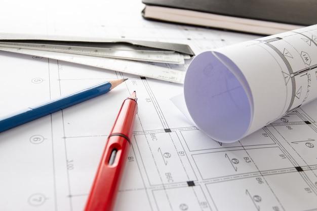 テーブル上の建築設計図と家の計画のロールと建築家の描画ツール。 Premium写真