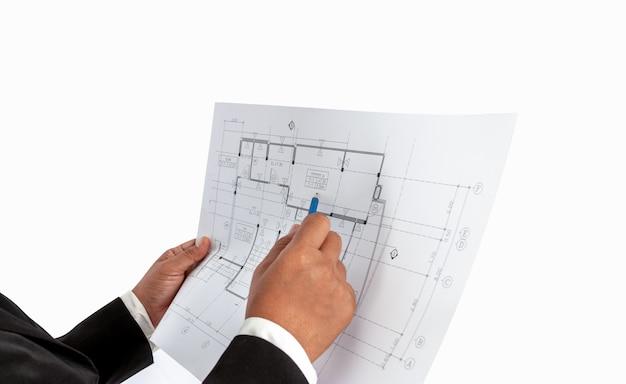 Бизнесмен в руке есть план строительства или архитектурный план, используемый для профессиональной профессиональной торговли, недвижимости, строительства. Premium Фотографии