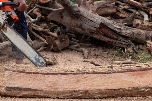 労働者はチェーンソーで作業します。チェーンソーをクローズアップ。木こりはチェーンソーで木を鋸で挽きます。のこぎり、ほこり、動きで木を切る男。 Premium写真