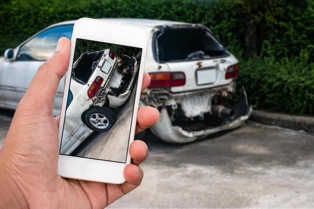 スマートフォンを持っている人の手を閉じるし、車の事故の写真を撮る Premium写真