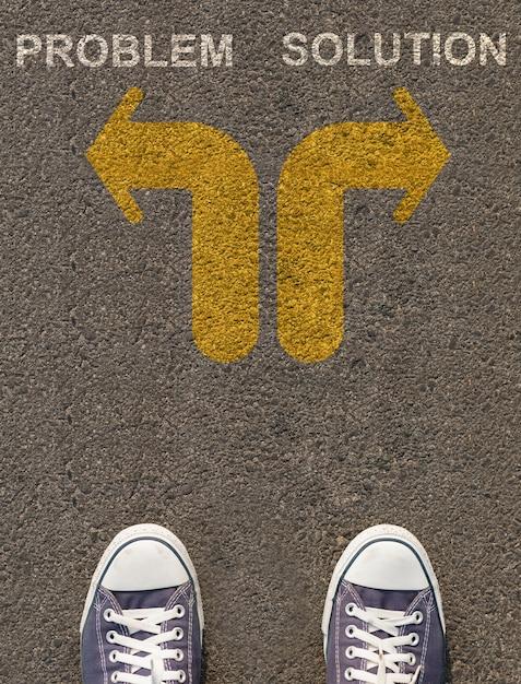 矢印の付いた道路上に立っている靴のペア Premium写真