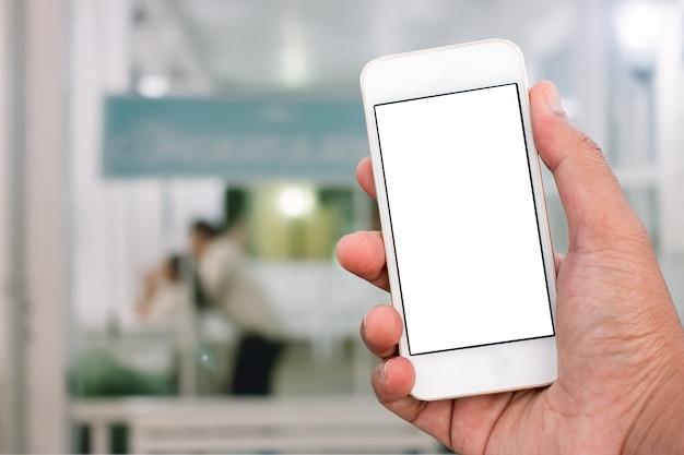 垂直位置、背景をぼかした写真 - モックアップテンプレートで空白の画面を持つモバイルスマートフォンを持っている手 Premium写真