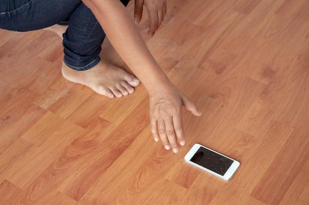 女性は家の床に落ちた電話を壊してしまった。 Premium写真