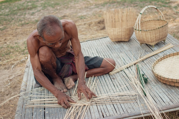 Дядя азиатский старик с плетеными инструментами. Premium Фотографии