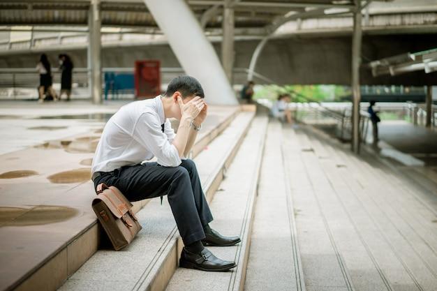 ビジネスマンは彼のハンドバッグを持って階段に座っています。彼は仕事に失敗した。彼は真面目で、疲れていて動揺しています。彼の仕事は成功ではありません。彼は自分のストレスから頭痛がします。 Premium写真