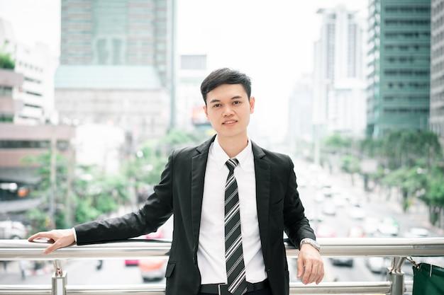 Мужчина одет в черный костюм, белую рубашку и галстук. Premium Фотографии
