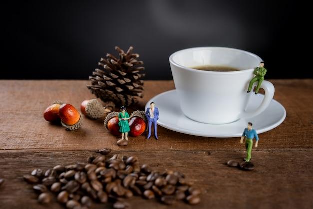 一杯の熱いブラックコーヒーが木製のテーブルの上にあり、コーヒー豆と小さなフィギュアモデルで飾られています。 Premium写真