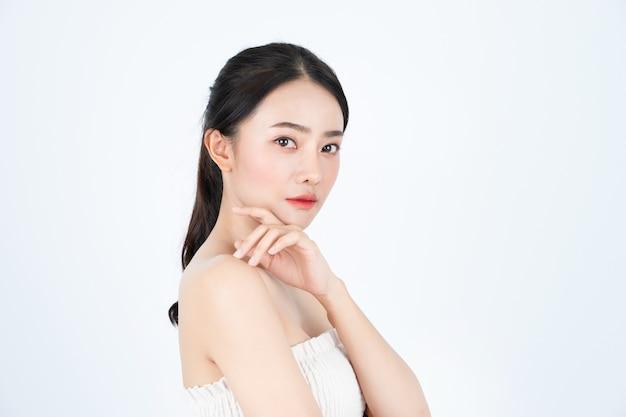 白いアンダーシャツの若いアジアの美しい女性は、健康で明るい肌をしています。 Premium写真
