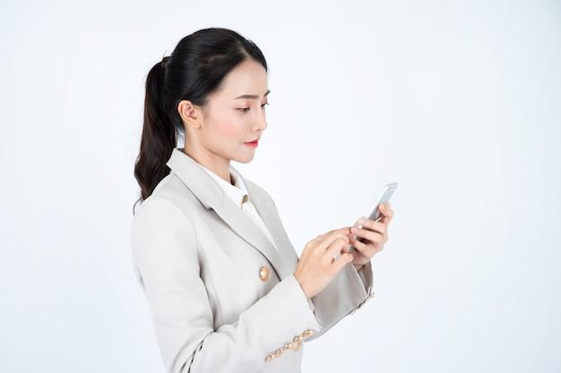 Молодая азиатская бизнес-леди в сером костюме, умна и уверена. менеджер думает о работе и пользуется телефоном. Premium Фотографии