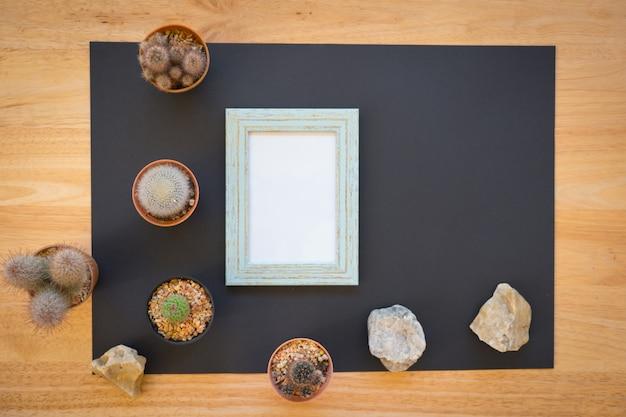 木製の背景にサボテンと空の写真フレームのモックアップ Premium写真