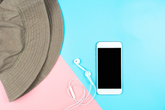 Макет смартфон с наушниками и шляпу на цветном фоне. Premium Фотографии