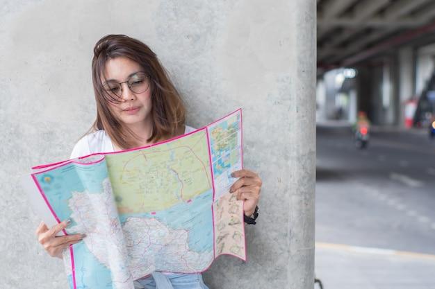 都市での計画旅行の地図を探している女性旅行者 Premium写真