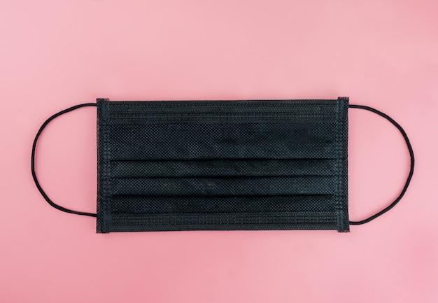 ピンクのテーブルに黒の健康マスク Premium写真