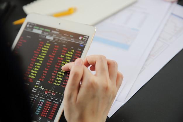 Женская рука, торгующая онлайн на планшете с деловой бумагой и кофе Premium Фотографии