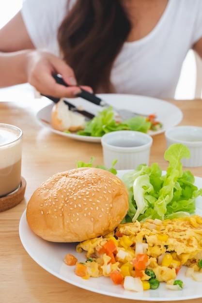 白い皿の上の朝食オムレツ、パン、ハンバーガー、野菜、ぼやけた背中で食べる Premium写真