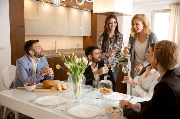 家庭で夕食をとり、白ワインを焼く若い友達 Premium写真