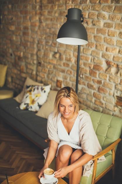 カフェの若いブロンドの女性 Premium写真