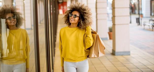 ショッピングの巻き毛を持つ若い黒人女性 Premium写真