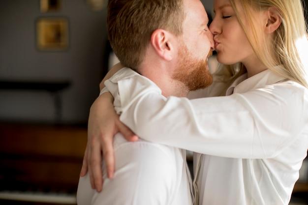 愛する若いカップルが部屋でキス Premium写真