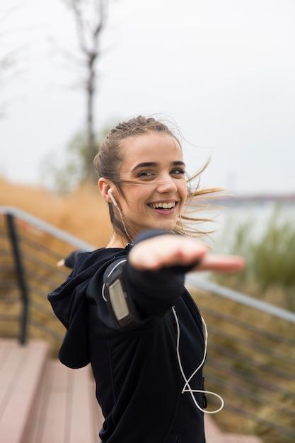 Спортсменка, вытянув руки во время прослушивания музыки на открытом воздухе Premium Фотографии
