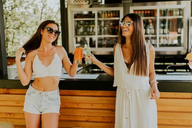 Молодые женщины пьют коктейль и веселятся у бассейна Premium Фотографии