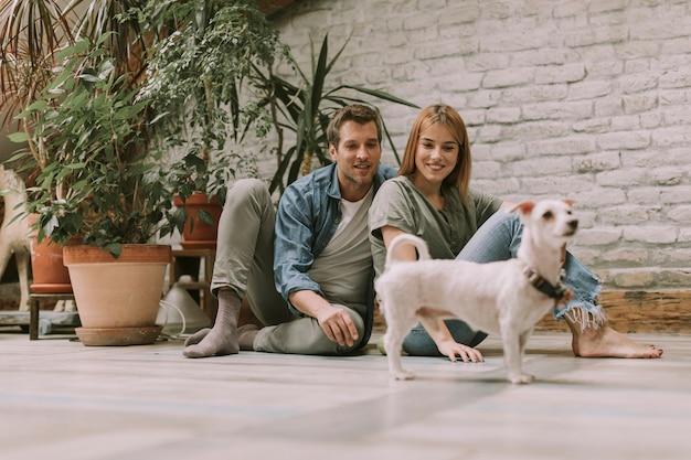 素朴なリビングルームの床に座っていると犬と遊ぶ若いカップル Premium写真