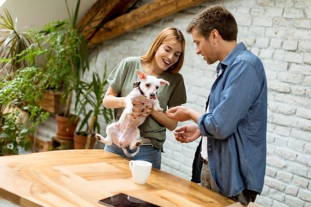 部屋でかわいい白い犬と愛情のあるカップル Premium写真