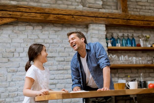 かわいい女の子と台所でパスタを準備する彼女のハンサムなお父さん Premium写真