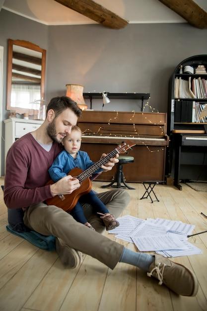 かわいい女の子と彼女のハンサムな父親はギターを弾いていると部屋に座っている間笑顔 Premium写真