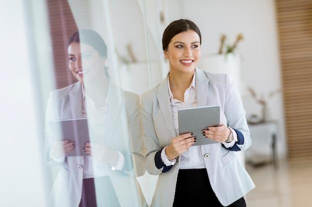 オフィスでタブレットを持つ若い女 Premium写真