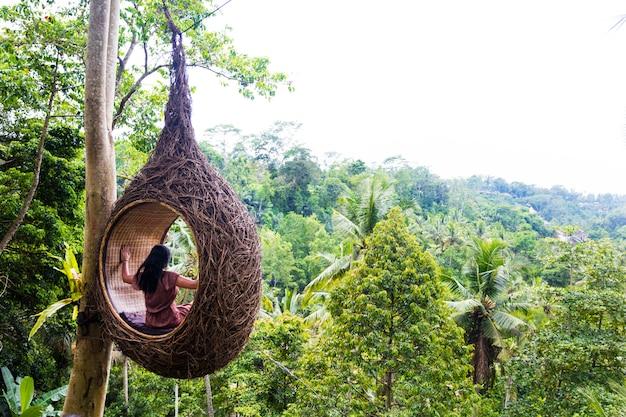 女性観光客はバリ島の木の上の大きな鳥の巣に座っています。 Premium写真
