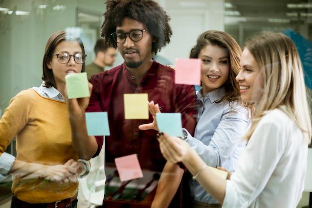 Молодые деловые люди обсуждают перед стеклянной стеной, используя заметки и наклейки Premium Фотографии