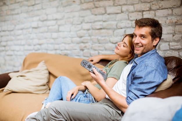 リラックスして自宅でテレビを見ている若いカップルの笑顔 Premium写真