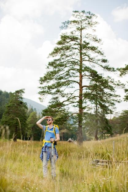 Молодой человек, наблюдая во время походов в солнечный день Premium Фотографии