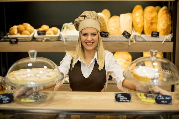 パン屋さんに笑みを浮かべて焼きたてのパンと女性のパン屋の肖像画 Premium写真